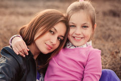 Lifestyle capture of happy mother and preteen daughter having fun outdoor. Loving family spending time together on the walk. Cozy weekend Royalty Free Stock Photo