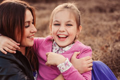 Lifestyle capture of happy mother and preteen daughter having fun outdoor. Loving family spending time together on the walk. Stock Image