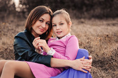 Lifestyle capture of happy mother and preteen daughter having fun outdoor. Loving family spending time together on the walk. Royalty Free Stock Photos