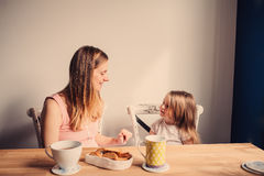 Lifestyle capture of happy pregnant mother and baby girl having breakfast at home Stock Image