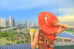 Singapore woman aperitif. Lifestyle caucasian woman in wide hat drinking aperitif at rooftop cityscape skyline. Tourist enjoying above aerial view of Singapore royalty free stock photos