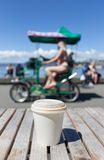 Lifestyle and coffee. A plastic coffee cup on a wooden table with blurred people outdoors Stock Photography