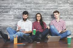 Lifestyle concept. Attractive businessmen and women with coffee cup, supplies and devices sitting on floor of wooden studio interior. Lifestyle concept Royalty Free Stock Photos