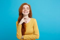 Lifestyle concept - Close up Portrait young beautiful attractive ginger red hair girl playing with her hair with shyness. Blue Pastel Background. Copy space Royalty Free Stock Photography