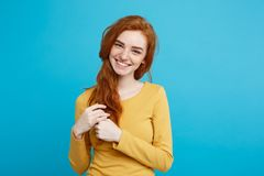 Lifestyle concept - Close up Portrait young beautiful attractive ginger red hair girl playing with her hair with shyness. Blue Pastel Background. Copy space Stock Photography
