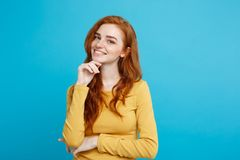 Lifestyle concept - Close up Portrait young beautiful attractive ginger red hair girl playing with her hair with shyness. Blue Pastel Background. Copy space Royalty Free Stock Photo