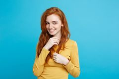 Lifestyle concept - Close up Portrait young beautiful attractive ginger red hair girl playing with her hair with shyness. Blue Pastel Background. Copy space Stock Photo