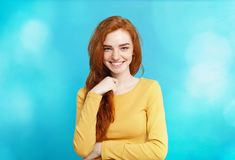 Lifestyle concept - Close up Portrait young beautiful attractive ginger red hair girl playing with her hair with shyness. Blue Pastel Background. Copy space royalty free stock photos