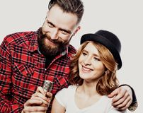 Lifestyle concept. Happy couple singing in karaoke over white background,. Happy couple singing in karaoke over white background Royalty Free Stock Image