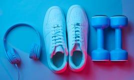 Lifestyle concept. Dumbbells, headphones, sneakers. Retro wave, neon light, ultraviolet. Top view, minimalism royalty free stock image