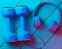 Lifestyle concept. Dumbbells with headphones on wooden background. Retro wave, blue red neon light, ultraviolet. Top view, minimalism royalty free stock photography