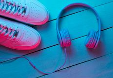 Lifestyle concept. Sneakers and headphones on wooden background. Retro wave, blue red neon light, ultraviolet. Top view, minimalism royalty free stock images