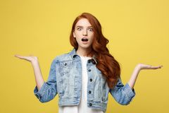 Lifestyle Concept: Surprised young woman with hand on side over golden yellow background. Looking at camera. Lifestyle Concept: Surprised young woman with hand Royalty Free Stock Photos