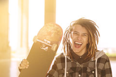Lifestyle concept of young guy  with skateboard and rasta hair w Royalty Free Stock Photos