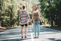 Lifestyle concept. Young happy family traveling adventure vacations. Couple travelers women and men stand on road and looking forward to a joint journey stock photo