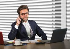 Lifestyle corporate company portrait of young happy and busy business man working at modern office talking on mobile phone by wind royalty free stock images