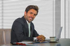 Lifestyle corporate company portrait of young happy and successful business man working relaxed at modern office sitting by window royalty free stock images