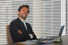 Lifestyle corporate company portrait of young happy and successful business man working relaxed at modern office sitting by window royalty free stock photos
