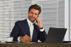 Lifestyle corporate company portrait of young happy and successful business man working relaxed at modern office sitting by window stock image