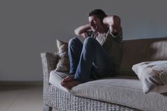 Lifestyle dramatic light portrait of young sad and depressed man sitting at shady home couch in pain and depression feeling stress stock photography