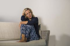 Lifestyle dramatic portrait of attractive and sad woman feeling frustrated and anxious sitting at home sofa couch depressed suffer royalty free stock image