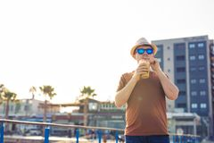 Lifestyle, drinks and people concept - man in sunglasses drinking coffee frappe from disposable paper cup outdoors.  Royalty Free Stock Photography