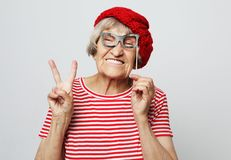 Lifestyle, emotion  and people concept: funny grandmother with fake glasses, laughs and ready for party stock photography