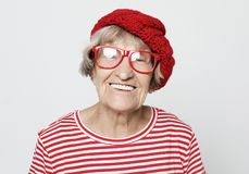 Lifestyle,emotion and people concept: funny grandmother posing over grey background stock photo