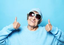 Lifestyle, emotion and people concept: Funny old lady wearing blue sweater, hat and sunglasses showing victory sign. Isolated on blue background stock photography
