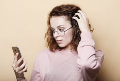 Lifestyle, emotional and people concept: Young beautiful curly woman with smartphone stock image