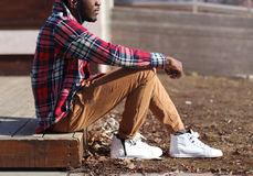 Lifestyle fashion photo stylish african man listens music enjoys sunset, wearing hipster plaid red shirt sitting in profile stock photography