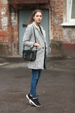 Lifestyle fashion portrait of beautiful young brunette woman in grey coat with black leather bag posing on street cloudy day Stock Image