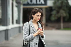 Lifestyle fashion portrait of beautiful young brunette woman in grey coat with coffee cup posing on street cloudy day. Lifestyle fashion portrait of beautiful Stock Photos