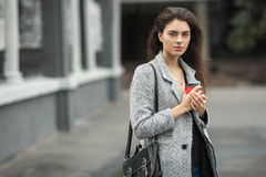 Lifestyle fashion portrait of beautiful young brunette woman in grey coat with coffee cup posing on street cloudy day. Lifestyle fashion portrait of beautiful Stock Photography