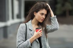 Lifestyle fashion portrait of beautiful young brunette woman in grey coat with coffee cup posing on street cloudy day. Lifestyle fashion portrait of beautiful Royalty Free Stock Images
