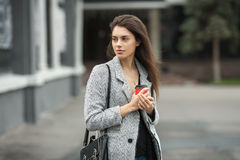 Lifestyle fashion portrait of beautiful young brunette woman in grey coat with coffee cup posing on street cloudy day. Lifestyle fashion portrait of beautiful Royalty Free Stock Photo