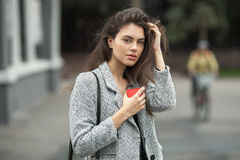 Lifestyle fashion portrait of beautiful young brunette woman in grey coat with coffee cup posing on street cloudy day. Lifestyle fashion portrait of beautiful Royalty Free Stock Photography