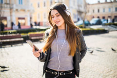 Lifestyle fashion portrait of young stylish hipster woman walking on street listen music. Summer sunny lifestyle fashion portrait of young stylish hipster woman Stock Photos