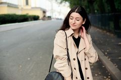 Lifestyle fashion portrait of young stylish hipster woman walking on street. Wearing cute trendy beige coat, smiling enjoy weekends. Soft colors, cool crazy royalty free stock photos