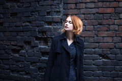 Lifestyle fashion portrait of young stylish woman walking on street. Against brick wall Stock Photos