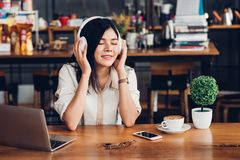 Lifestyle freelance woman he using earphones listening music dur Royalty Free Stock Photos