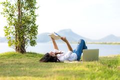 Lifestyle Girl enjoy listening music and reading a book and play laptop on the grass field of the nature park in the morning gree Royalty Free Stock Photos