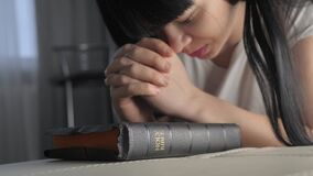 Lifestyle girl praying indoors at bedtime on bible. Religion concept evening prayer woman brunette hands on bible
