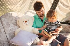 Father reading to his toddler kid, outdoor. Lifestyle, handsome father read a book to his cute little daughter outdoors, warm summer day, family relationship Stock Photo