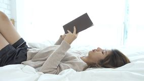 Lifestyle happy young Asian woman enjoying lying on the bed reading book pleasure in casual clothing at home. stock video