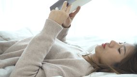 Lifestyle happy young Asian woman enjoying lying on the bed reading book pleasure in casual clothing at home. Relaxing lifestyle woman concept. Dolly shot stock footage