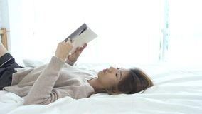 Lifestyle happy young Asian woman enjoying lying on the bed reading book pleasure in casual clothing at home. Relaxing lifestyle woman concept stock footage