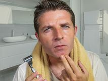 Lifestyle home portrait of attractive and concentrated man holding razor after shaving his face touching his chin at modern stock photos