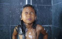 Lifestyle home portrait of sweet and happy female child having shower in the bathroom washing her hair in hygiene education royalty free stock photos