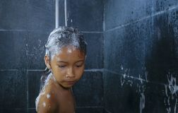 Lifestyle home portrait of sweet and happy female child having shower in the bathroom washing her hair in hygiene education stock photography